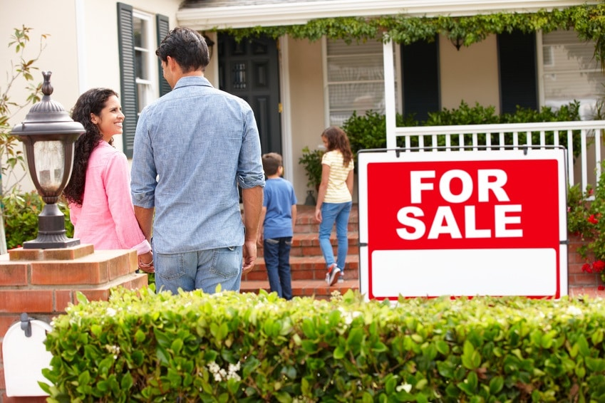 A couple considering buying a house with a for sale sign - get a building report Auckland concept