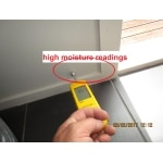 Non-invasive moisture testing probe reading moisture levels in an exterior wall
