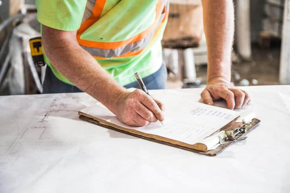 building inspector with clipboard doing building inspections