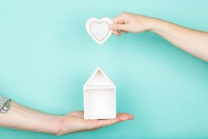 hands holding a heart and a home showing professionals can give information for first home buyers
