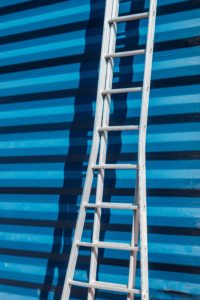 ladder leading on a blue building signifying getting on the property ladder