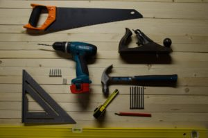 collection of tools including drill, hammer and saw that could be needed if you are buying a fixer upper in Auckland