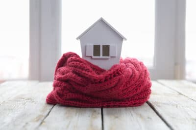Health home concept for landlord showing toy house wrapped in warm scarf