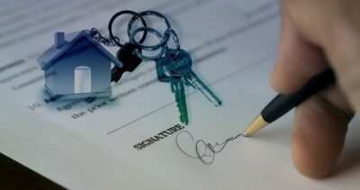hand signing one of the house sale options with a small house and keys